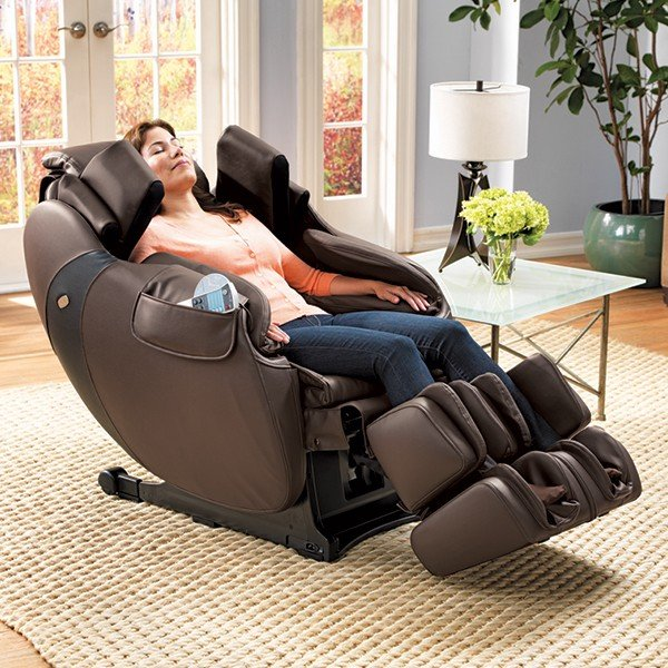 Brunette woman with eyes closed in brown massage chair