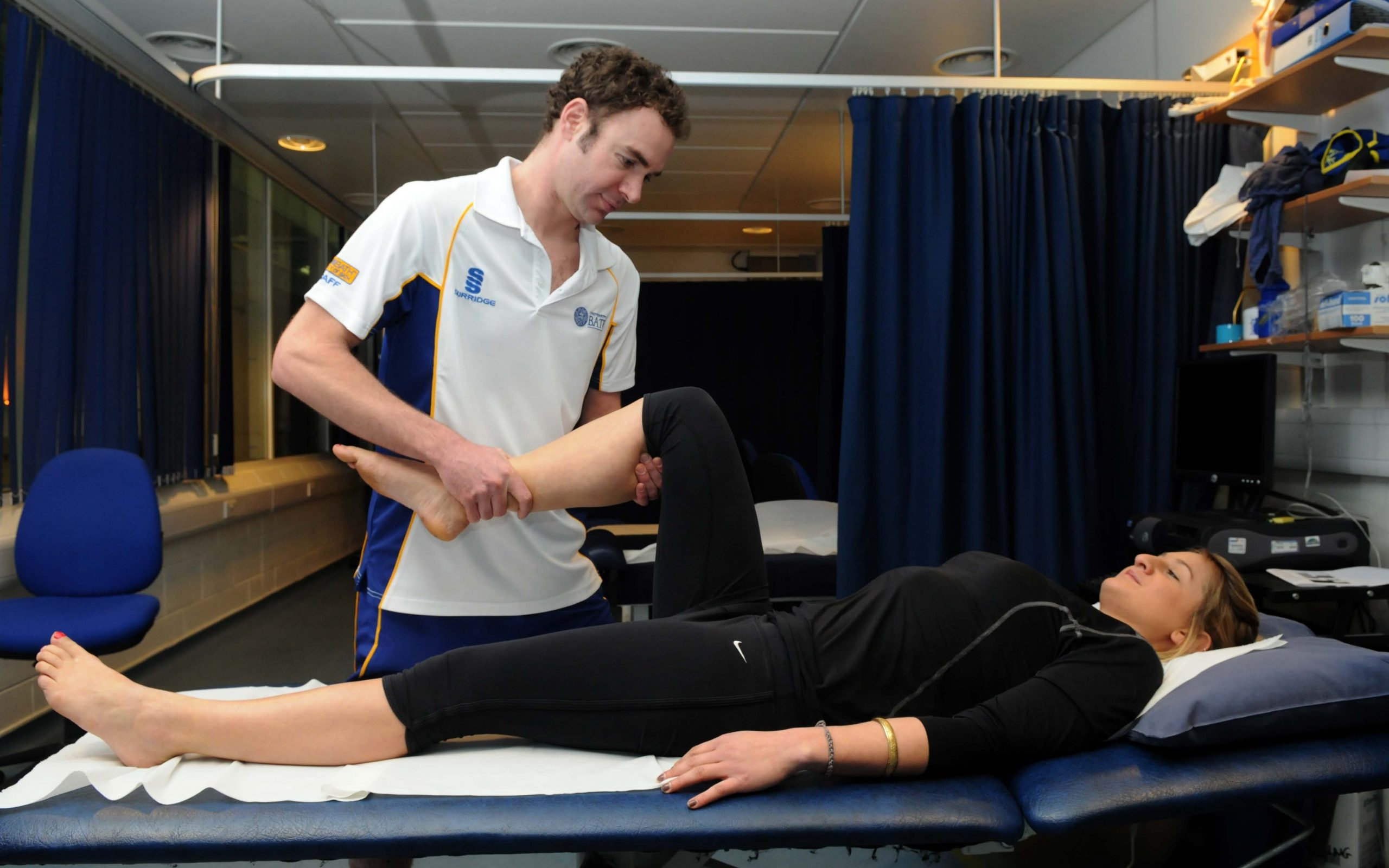Brunette male physiotherapist holding leg of blond woman while she lies down on table
