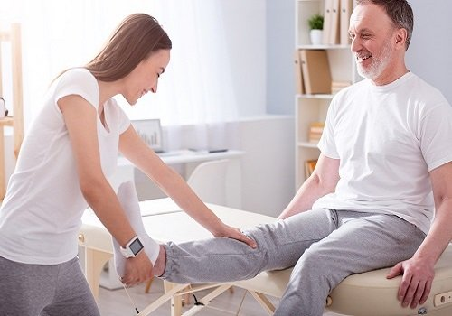 Brunette physiotherapist holding foot and knee of older man with grey beard sitting on massage table