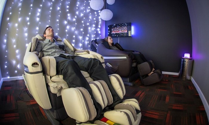 Man in white massage chair next to woman in black massage chair with a wall of lights behind them