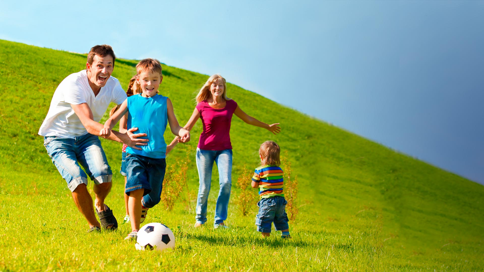 Family playing soccer in a green field with hills behind them