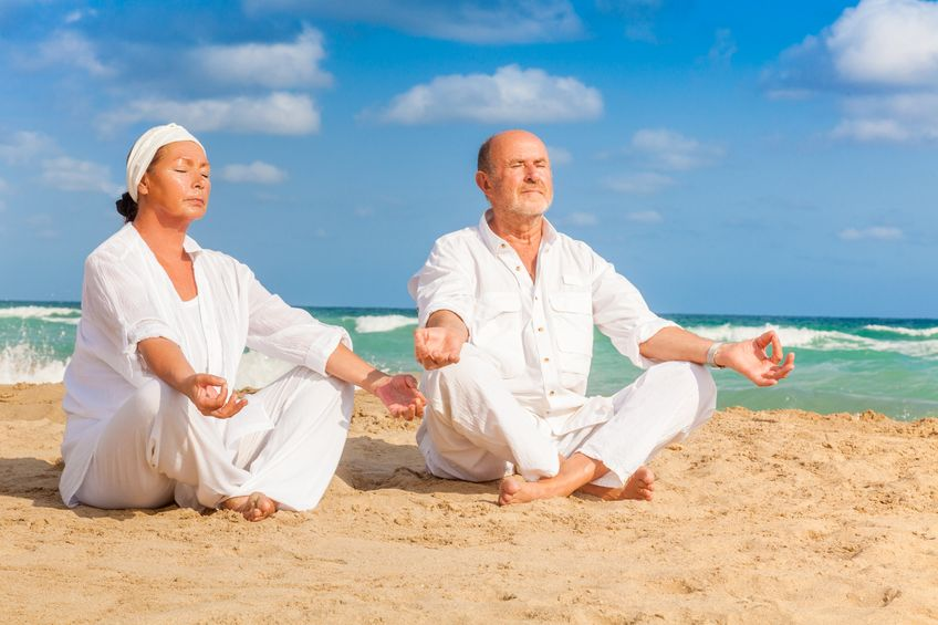 Older couple in white clothes meditating on beach