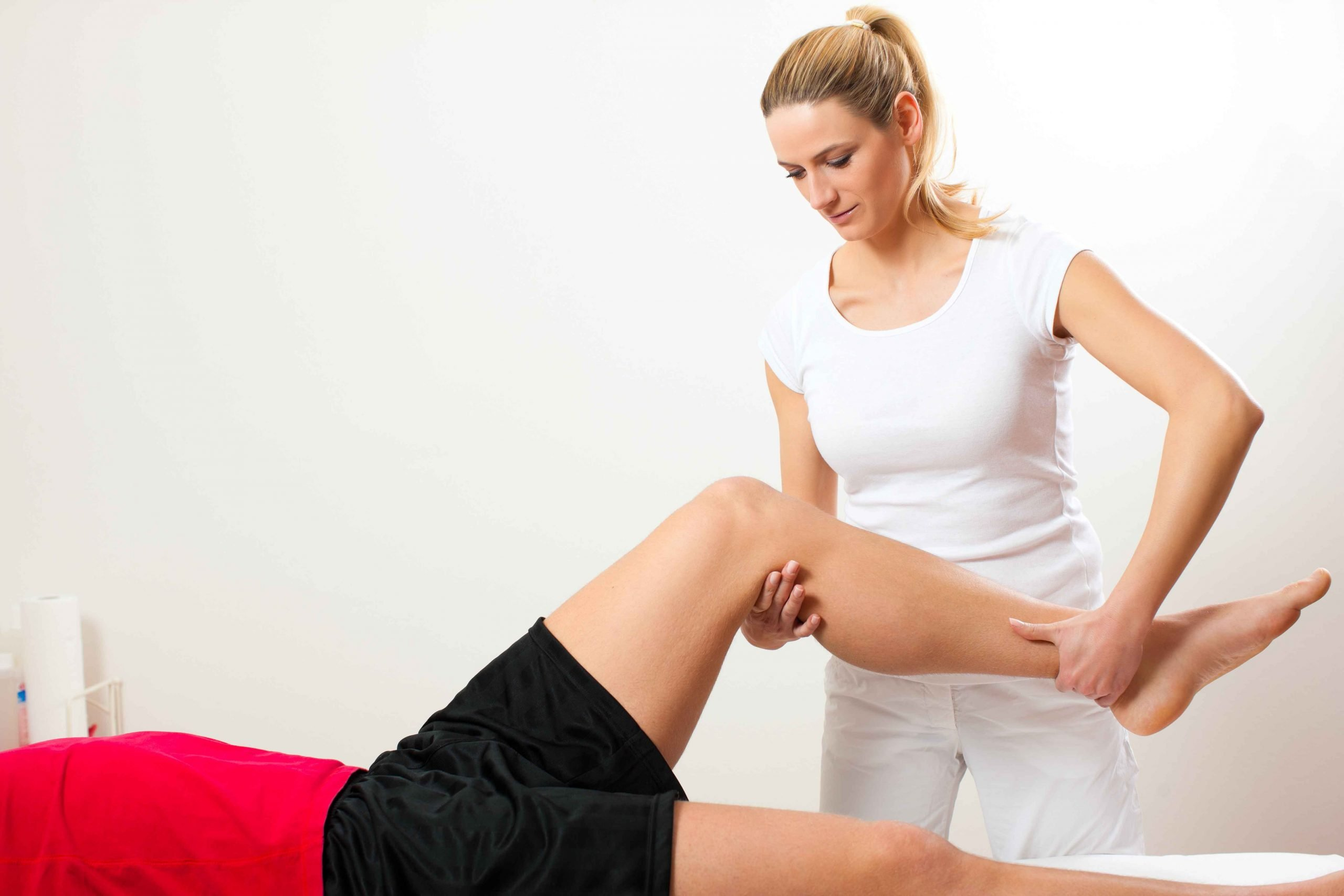 Female blonde physiotherapist holding knee and ankle of patient