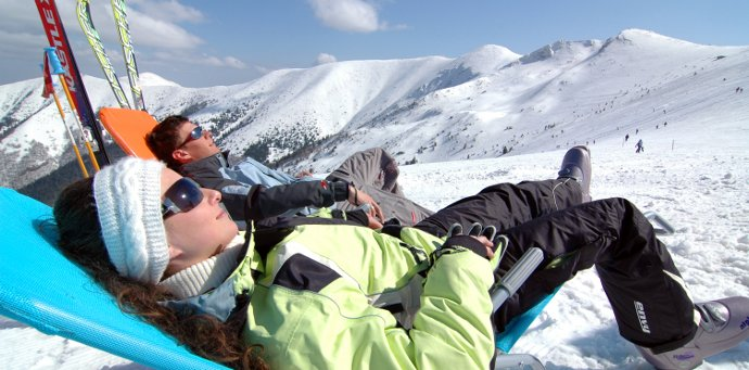 Couple relaxing in ski gear on a snowy mountain